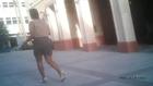 Brunette girl in beige sleeveless blouse, gray pencil skirt and white high heel stiletto pumps